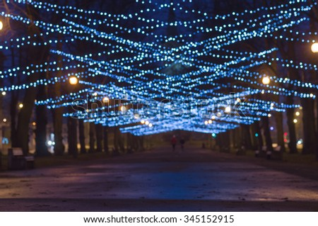 Blurred image of New Year and Christmas lighting decoration of city boulevard - stock photo