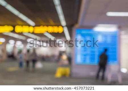 blurred image of people in the airport terminal, a man is looking at the departures board - stock photo