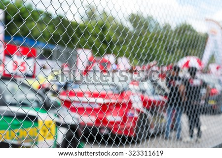 blurred image of racing car on track view from behind fence