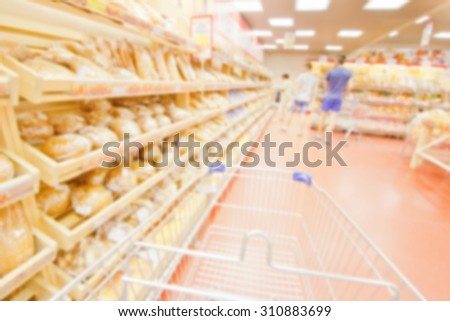 blurred image of shopping in supermarket with shopping cart - stock photo