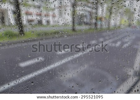 blurred image of street view through a car window covered in rain - stock photo