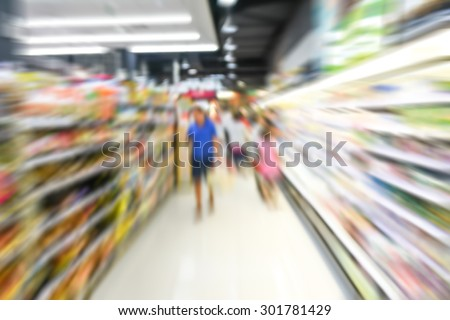 blurred image of supermarket people shopping motion blur - product shelf - business concept