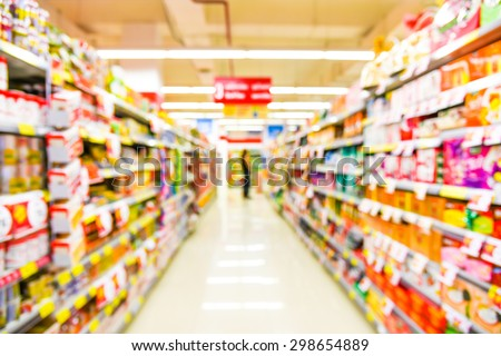 blurred image of supermarket people shopping - product shelf - business concept