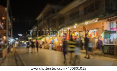Blurred image of tourists walking at night market
