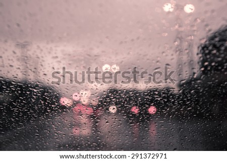 blurred image of traffic view through a car windscreen covered in rain,vintage filter - stock photo