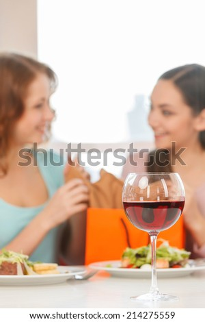 blurred image of two teenage girls talking in cafe. Two smiling girls have coffee time - stock photo