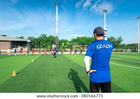 blurred image ofCoach is coaching Children Training In Soccer Team - stock photo