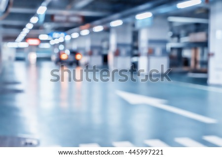 Blurred image/ Parking garage - interior shot of multi-story car park, underground parking with cars.  - stock photo
