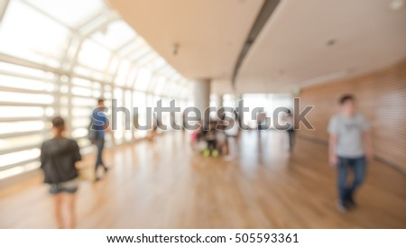 Blurred image people enjoying sightseeing from a modern observation desk of skyscraper in Singapore. Abstract background of people walking, seating and standing at huge observatory. Panorama view.