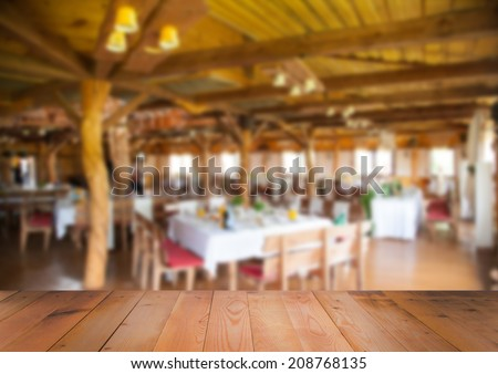 Blurred interior of restaurant with wooden surface - stock photo