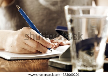 blurred interior of retro kitchen and closeup of pen and glass of water  - stock photo