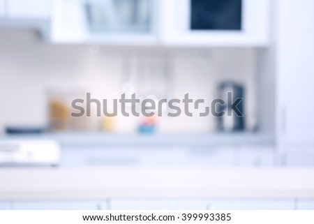 Blurred kitchen interior in light tones with white furniture - stock photo