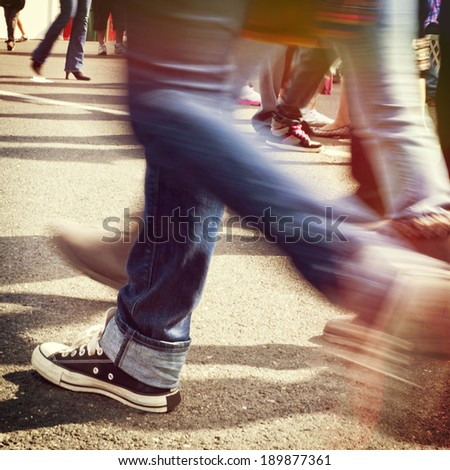 Blurred legs walking on concrete pavement, instagram style filter - stock photo