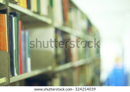 Blurred library with books on the shelf, chairs table and the light from windows in public library. selective focus Blurred effect. Background for your pictures - stock photo