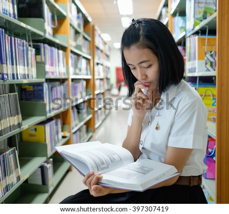 blurred library with books on the shelf, selective focus on thai young woman student in uniform is reading a book - stock photo