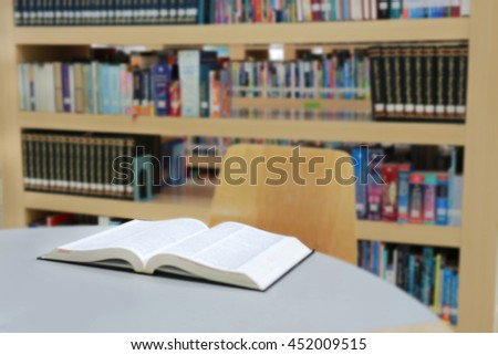 Blurred library with open book on table desk and bookshelf, abstract blur defocused background - stock photo