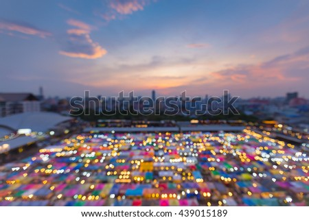Blurred lights multiple colours weekend market with city downtown background, aerial view - stock photo