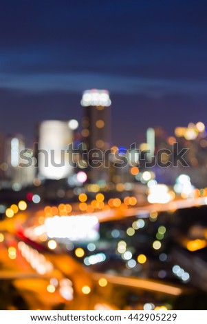 Blurred lights night view over highway road and office building, abstract background - stock photo