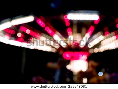 Blurred lights of a fairground carousel against a black background - stock photo
