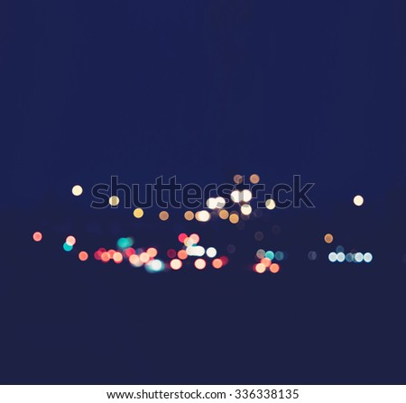 Blurred lights of distant town, copy space. A beautiful background on dark. toned image. Blurred night city background with circle lights. Blur backgrounds traffic lights. - stock photo