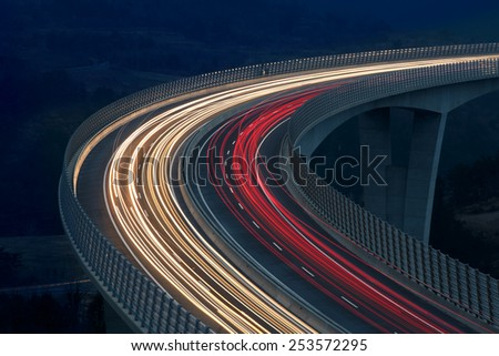Blurred lights of vehicles driving on a tall viaduct with wind barriers, long exposure - stock photo