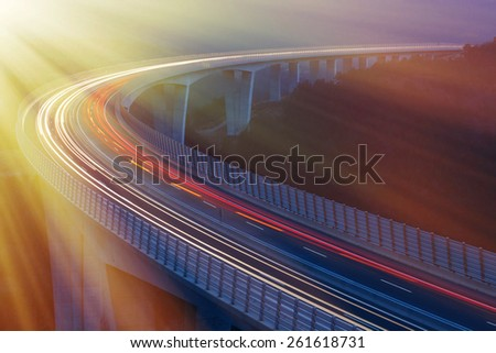 Blurred lights of vehicles driving on a tall viaduct with wind barriers, long exposure, sunlit with golden rays. Morning traffic. - stock photo