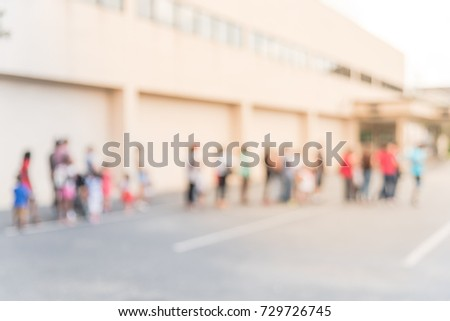 Blurred long people queuing for check-in at public event in Houston, Texas, US. Abstract background large group of diverse multiethnic visitors crowd family member, adult, kid, toddler waiting.