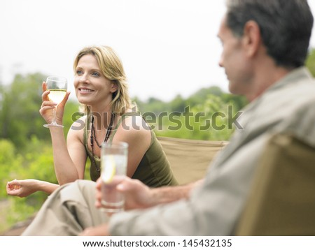 Blurred man looking at a happy woman drink wine outdoors - stock photo