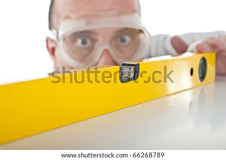 Blurred man with goggles working with bubble level - stock photo
