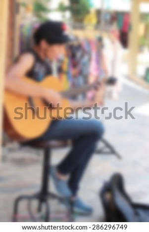 blurred men playing the guitar