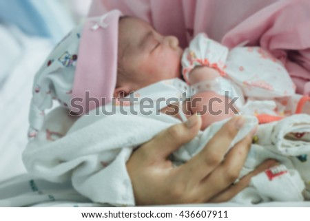 blurred mother hands holding newborn baby boy : mother day, health care and medical and people concept