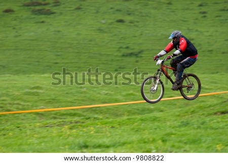 Blurred motion fly on downhill mountain bike race - stock photo