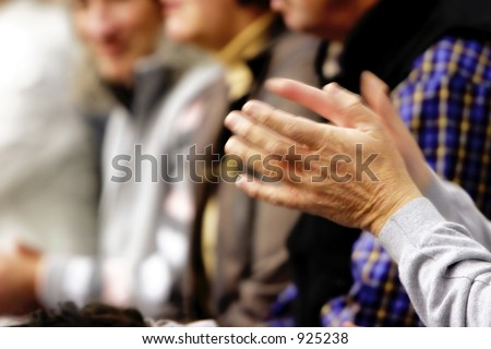 Blurred motion image (slow shutter speed) of a pair of hands clapping in a crowd. - stock photo