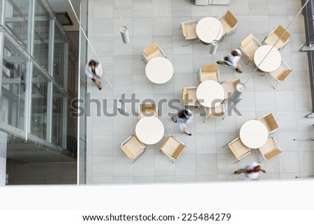 Blurred motion of businesswomen walking at office canteen - stock photo