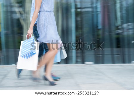 Blurred motion of couple with paper bags walking along the street - stock photo