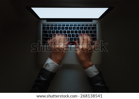 Blurred motion of hands typing on laptop late at night, view from above - stock photo