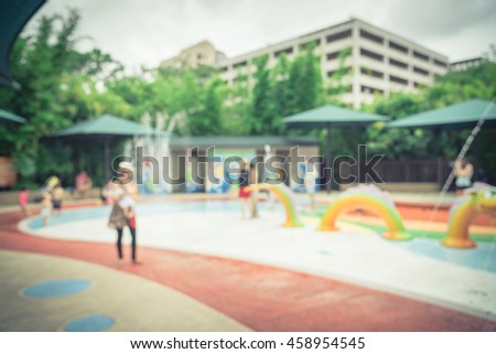 Blurred motion of kids having fun play with water at playground in summer time. Activities for children and family at urban outdoor aquatic park with water sprinkles and fountain. Vintage filter look.