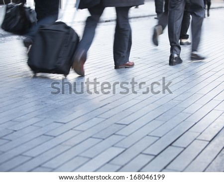 Blurred motion of legs walking in a busy business environment
