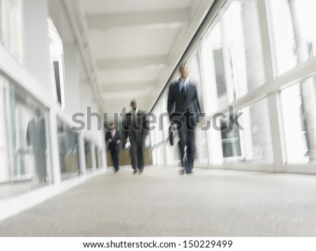 Blurred motion of multiethnic businessmen walking in office corridor - stock photo