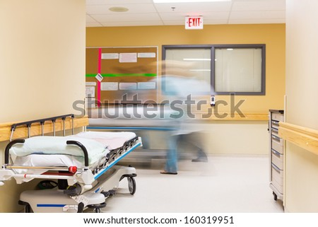 Blurred motion of nurses with stretcher walking in hospital corridor - stock photo