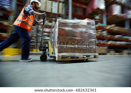 Blurred motion shot of warehouse worker wearing hardhat and reflective jacket pushing moving cart with boxes along isle between tall racks