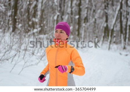 Blurred motion: winter running in park: happy woman runner jogging in snow, outdoor sport and fitness concept  - stock photo