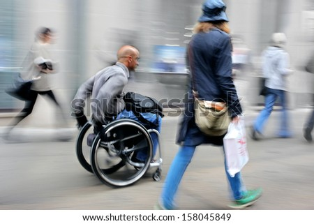 blurred movement disabled on a city street - stock photo