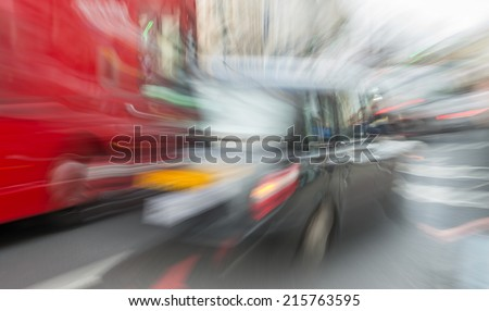 Blurred movement of London black cab and red bus in city traffic. - stock photo