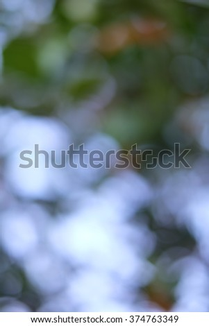Blurred natural outdoors background in green and blue sky tones. - stock photo