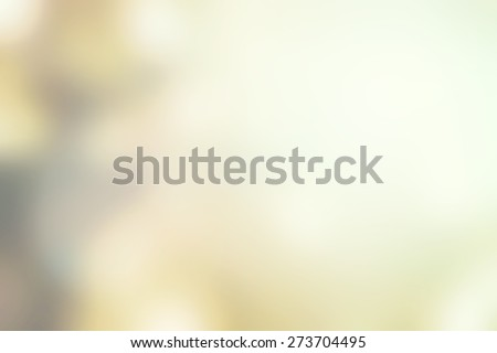 Blurred nature background of tree leaves looking upward to the sky with bokeh and sun flare in yellow green color tone   - stock photo
