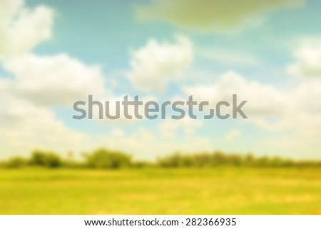 Blurred nature green field with sunny sky covered in clouds  - stock photo