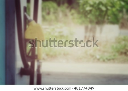 Blurred nozzle fuel in gas station wallpaper background, process vintage tone