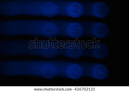 Blurred numbers 1, 2, 3, 4, 5, 6, 7, 8, 9 on the TV remote. The numbers shines with blue on a black background and leaves light trail behind. - stock photo