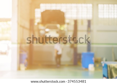 Blurred of car technician repairing the car in garage background, Interior of a car repair station,Cars servicing at Service station,car mechanic work at repair service station garage,vintage color. - stock photo